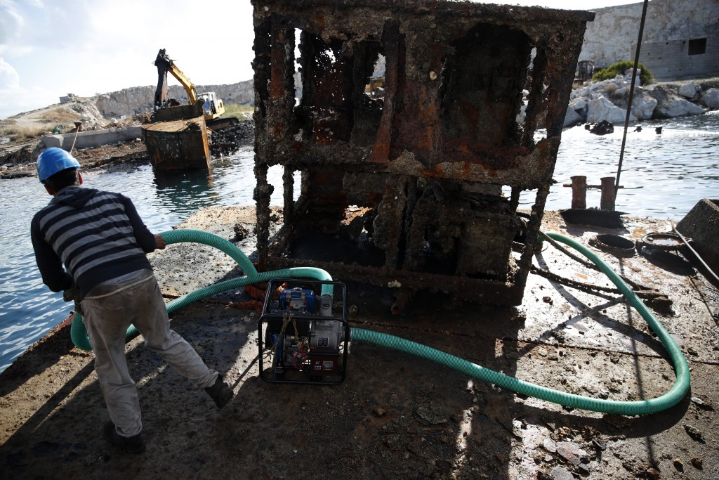 A worker pumps out water from a shipwreck during a raising operation, on Salamina island, west of Athens, on Friday, Nov. 8, 2019. Greece this year is...