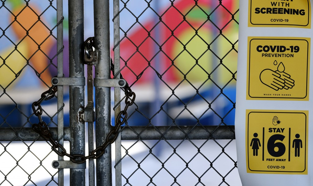 FILE - In this July 13, 2020, file photo, a chain-link fence lock is seen on a gate at a closed Ranchito Elementary School in the San Fernando Valley ...