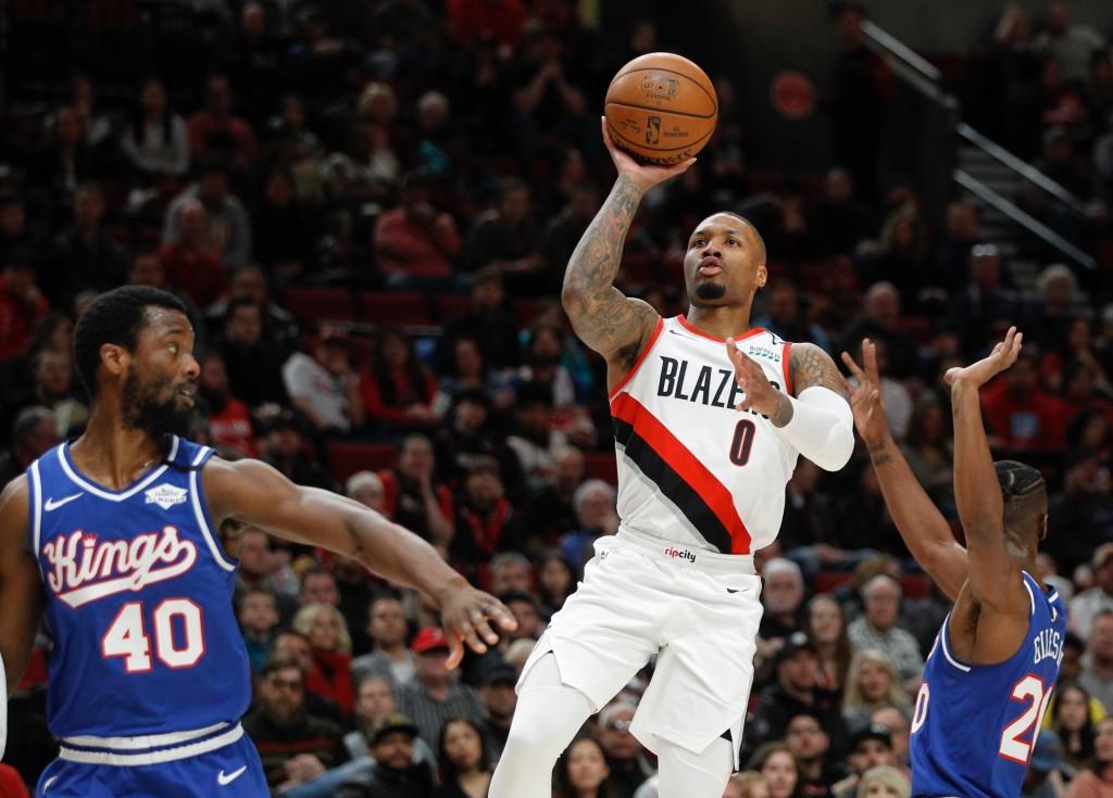 FILE - In this Saturday, March 7, 2020, file photo, Portland Trail Blazers guard Damian Lillard, center, shoots as Sacramento Kings forward Harrison B...