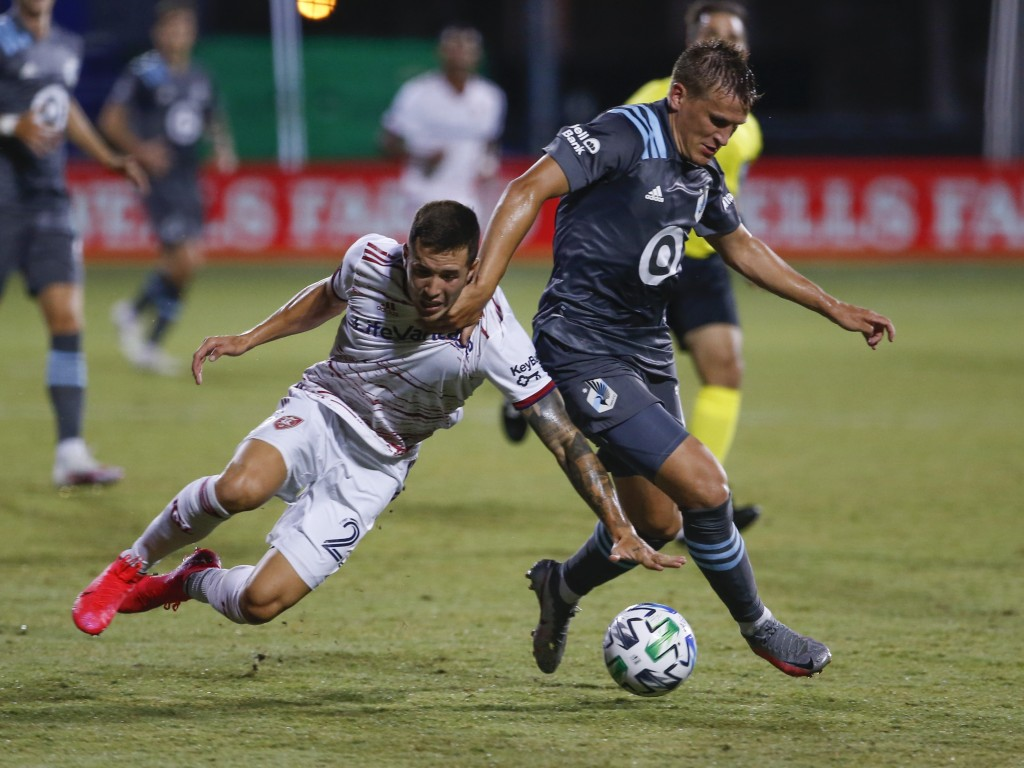 Real Salt Lake defender Aaron Herrera (22) and Minnesota United midfielder Robin Lod, right, battle for the ball during the first half of a soccer mat...