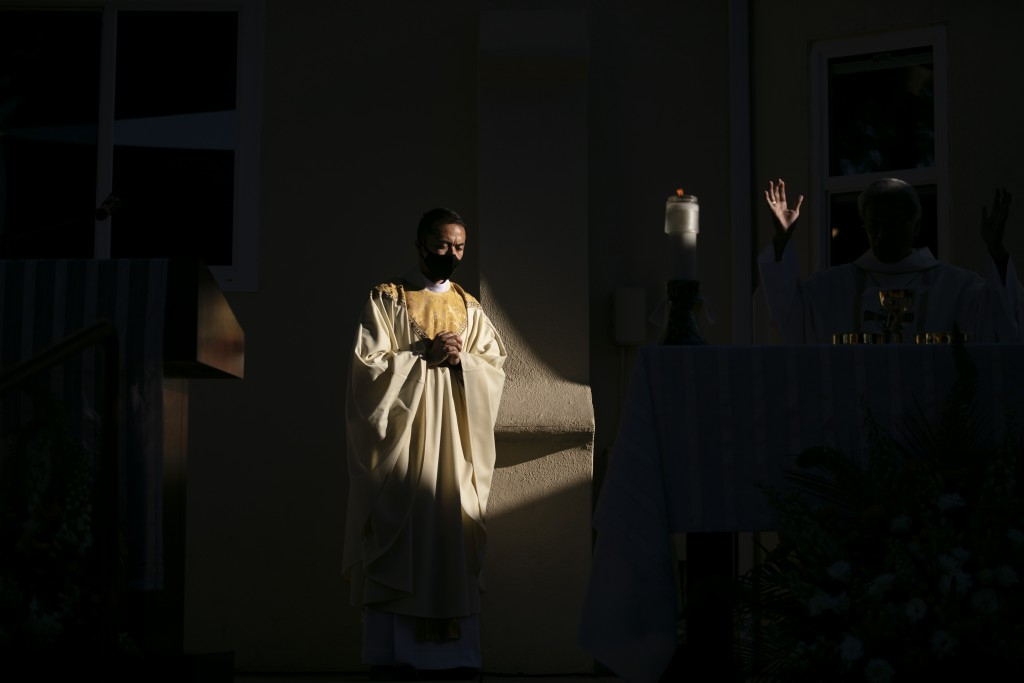 A shaft of sunlight falls on Justin Claravall during an ordination ceremony for the new priest at Dolores Mission Church in Los Angeles, Wednesday, Ju...
