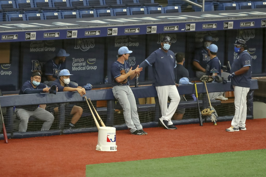 FILE - In this July 16, 2020, file photo, members of the Tampa Bay Rays await the start of a team baseball scrimmage in St. Petersburg, Fla. Public he...