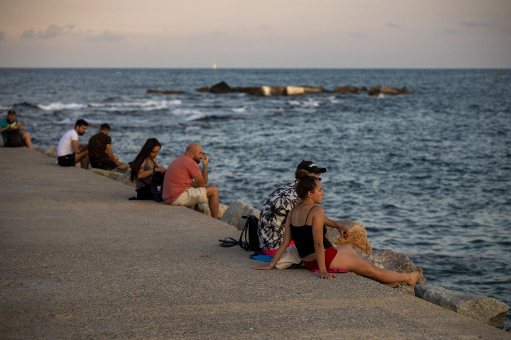 People sit on a breakwater near the beach in Barcelona, Spain, Friday, July 17, 2020. Health authorities are asking Barcelona's 5.5 million residents ...