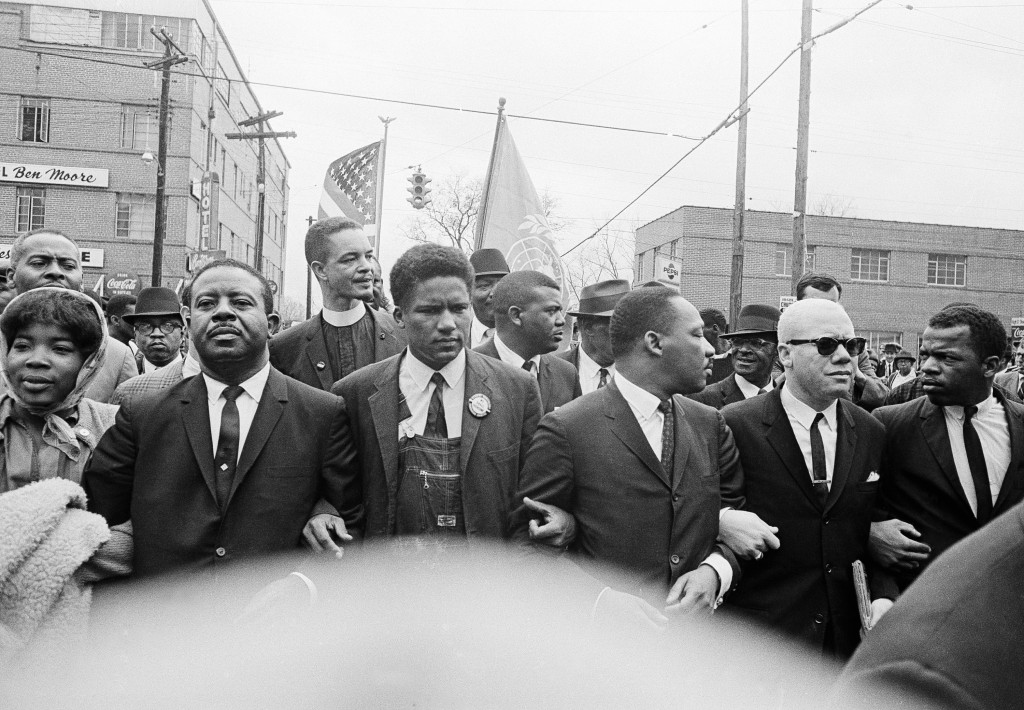 FILE - In this March 17, 1965, file photo, Dr. Martin Luther King Jr., fourth from left, foreground, locks arms with his aides as he leads a march of ...