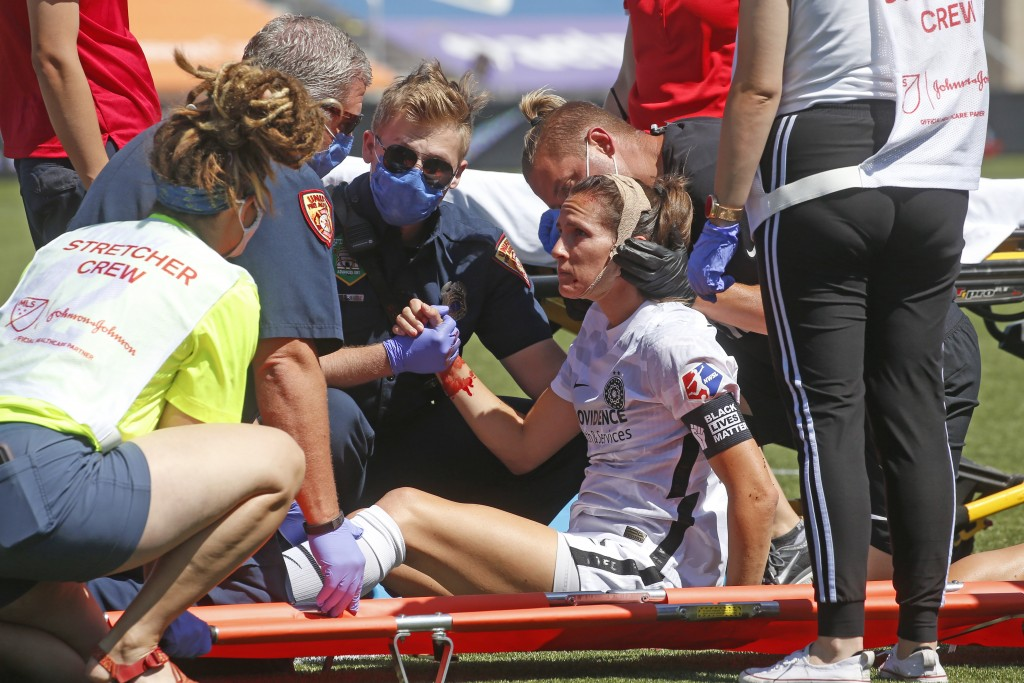 Portland Thorns' Katherine Reynolds is helped after an injury during the first half of an NWSL Challenge Cup soccer match against the North Carolina C...