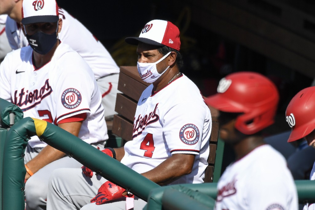 Washington Nationals manager Dave Martinez wears a mask as he watches an intersquad baseball game at Nationals Park in Washington, Friday, July 17, 20...