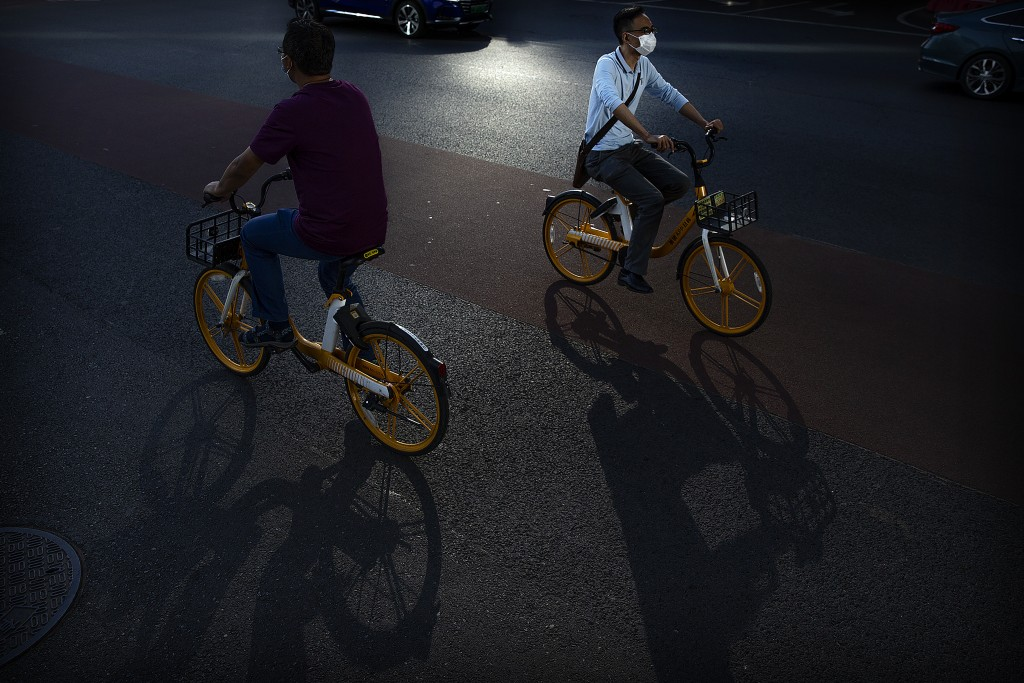 People wear face masks to protect against the coronavirus as they ride bicycles on a street in the central business district in Beijing, Wednesday, Ju...