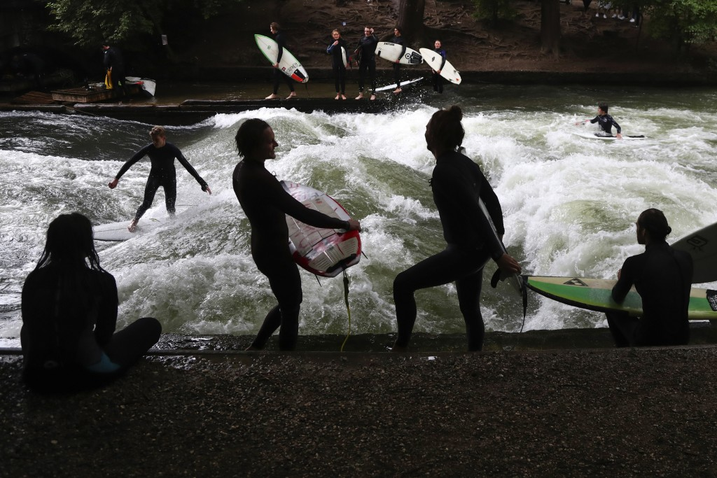 """A surfer rides on an artificial wave in the river """"Eisbach"""" in the """"English Garden"""" park of Munich, Germany, Thursday, July 16, 2020. (AP Photo/Matthi..."""