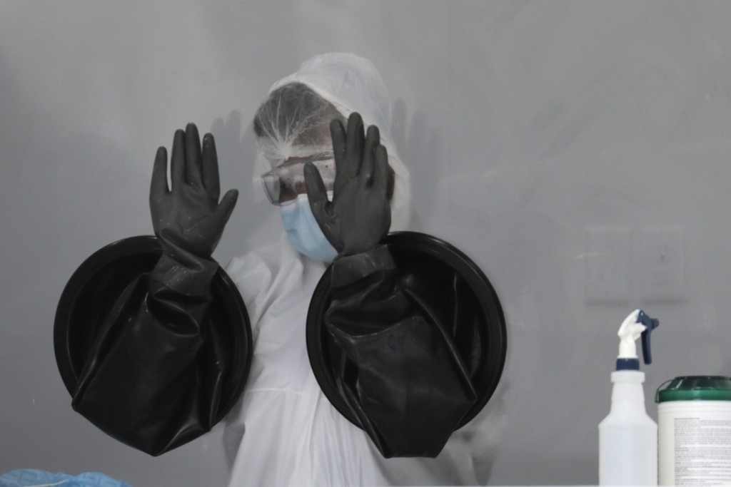 A health care worker air dries her gloves after sanitizing her equipment while working at a walk-up COVID-19 testing site during the coronavirus pande...