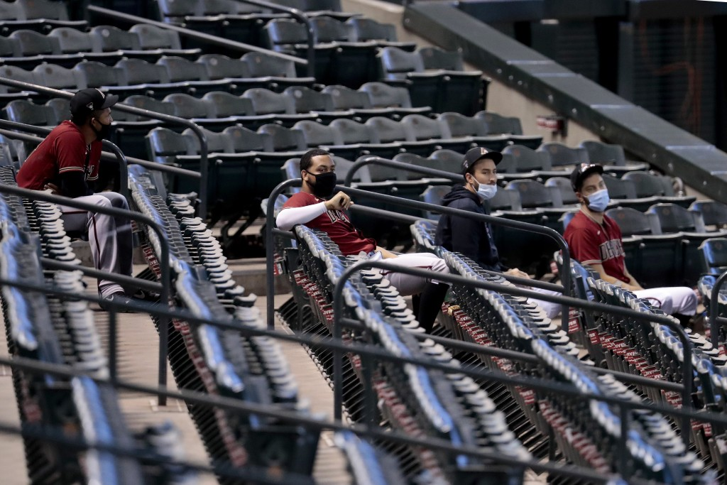 FILE - In this July 16, 2020, file photo, Arizona Diamondbacks players watch from the stadium seats during an intrasquad game at Chase Field, in Phoen...