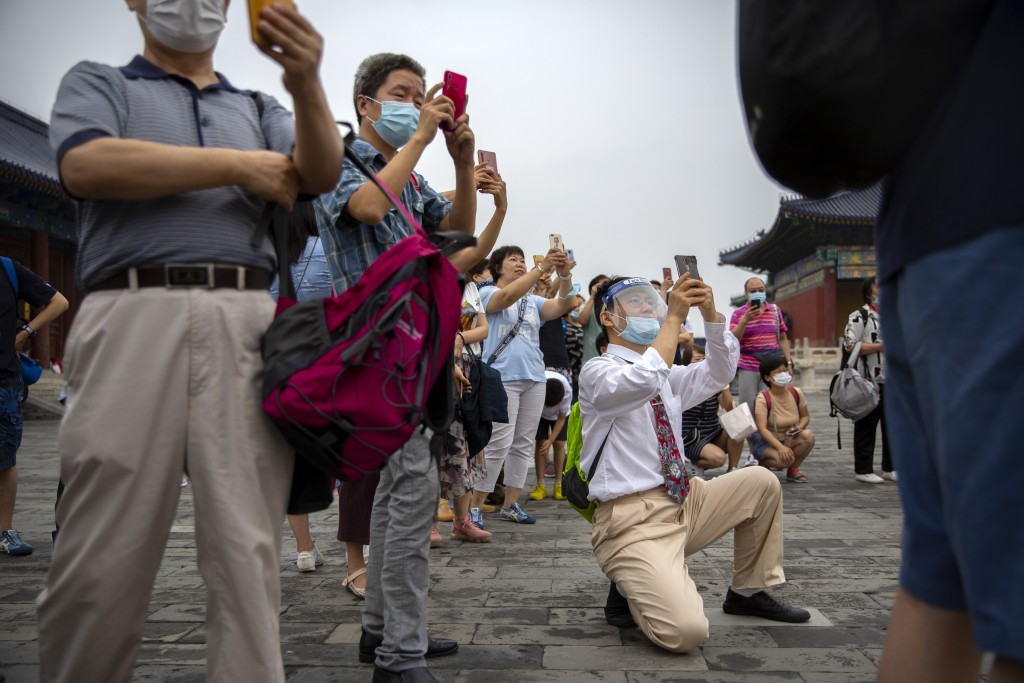 Parents wearing face masks to protect against the coronavirus take photos of students as they pose for a group photo at the Temple of Heaven in Beijin...