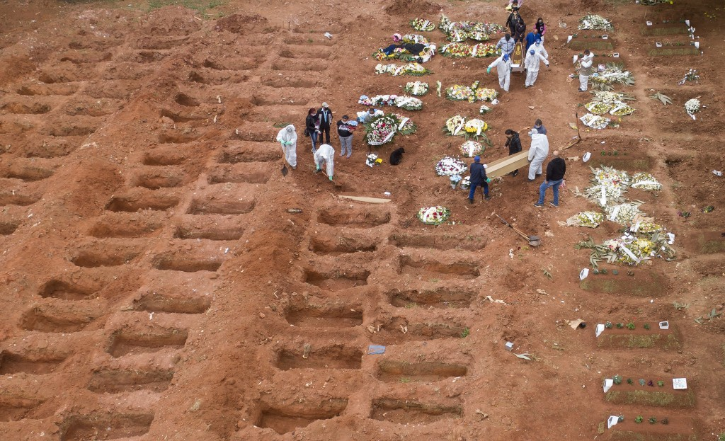 Cemetery workers in protective clothing bury three victims of the new coronavirus at the Vila Formosa cemetery in Sao Paulo, Brazil, Wednesday, July 1...
