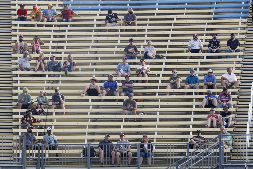 Fans sit in spread out groups as they watch the IndyCar Series auto race Friday, July 17, 2020, at Iowa Speedway in Newton, Iowa. (AP Photo/Charlie Ne...
