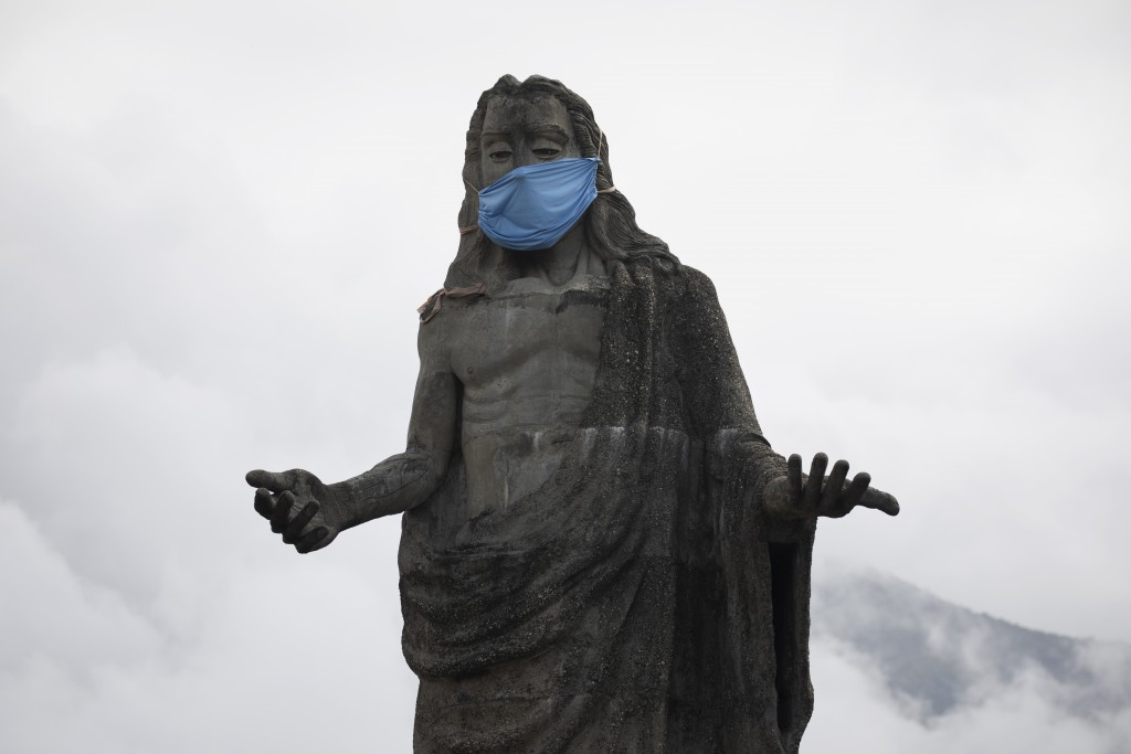 A protective face mask adorns a Jesus Christ statue as a reminder for residents to wear masks as a precaution against the spread of the new coronaviru...