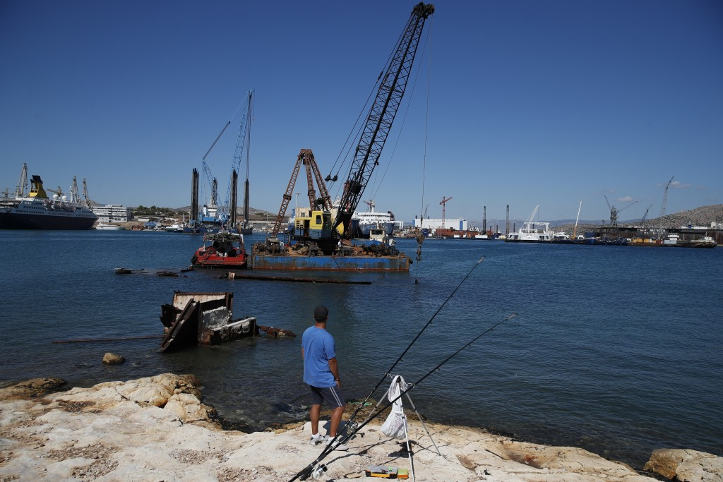 A man fishes as a floating crane prepares to raise a shipwreck, on Salamina island, west of Athens, on Monday, Aug. 26, 2019. Greece this year is comm...