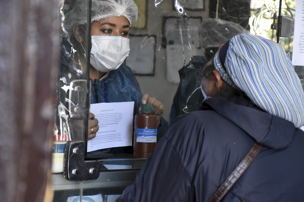 A woman buys chlorine dioxide at a pharmacy in Cochabamba, Bolivia, Friday, July 17, 2020. Long lines form every morning in Cochabamba, one of the Bol...