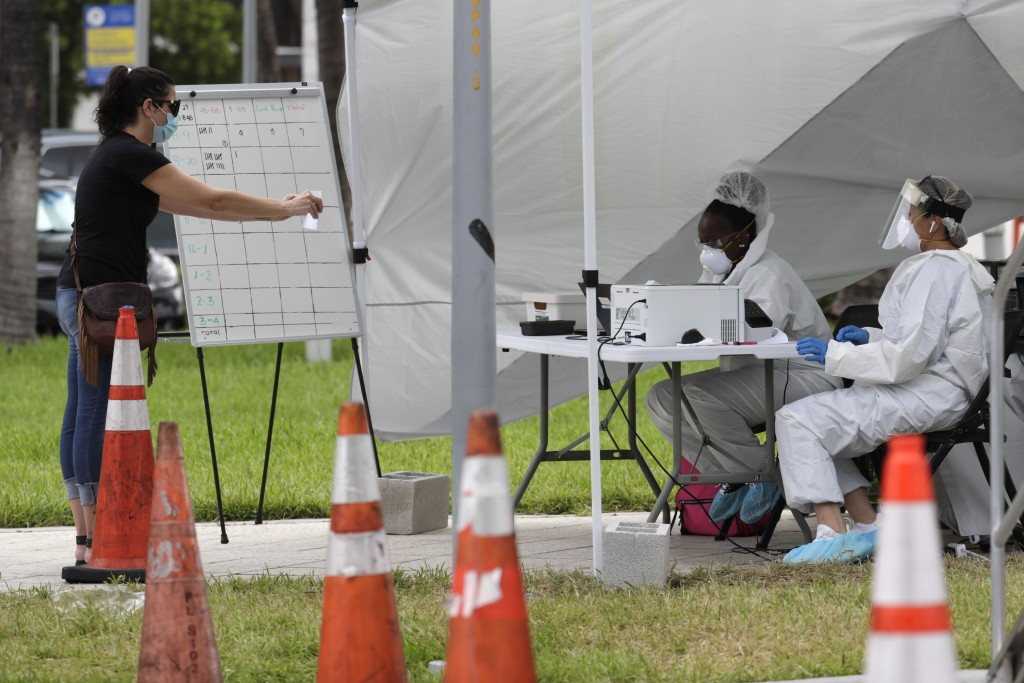 Health care workers take information from people in line at a walk-up COVID-19 testing site during the coronavirus pandemic, Friday, July 17, 2020, in...