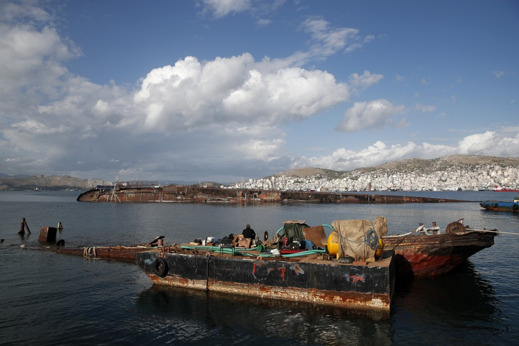 A diver takes a break on a half sunken ship in Damari, an area with eleven shipwrecks, on Salamina island, west of Athens, on Friday, Nov. 8, 2019. Gr...
