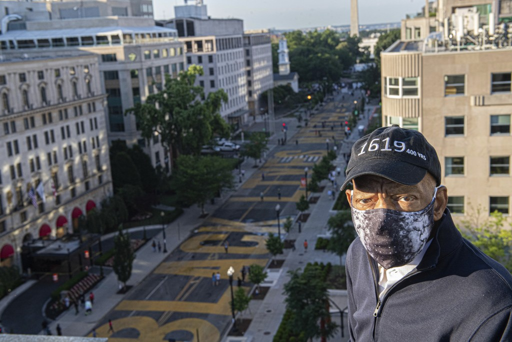 In this June 7, 2020 photo provided by the Executive Office of District of Columbia Mayor Muriel Bowser, John Lewis looks over a section of 16th Stree...