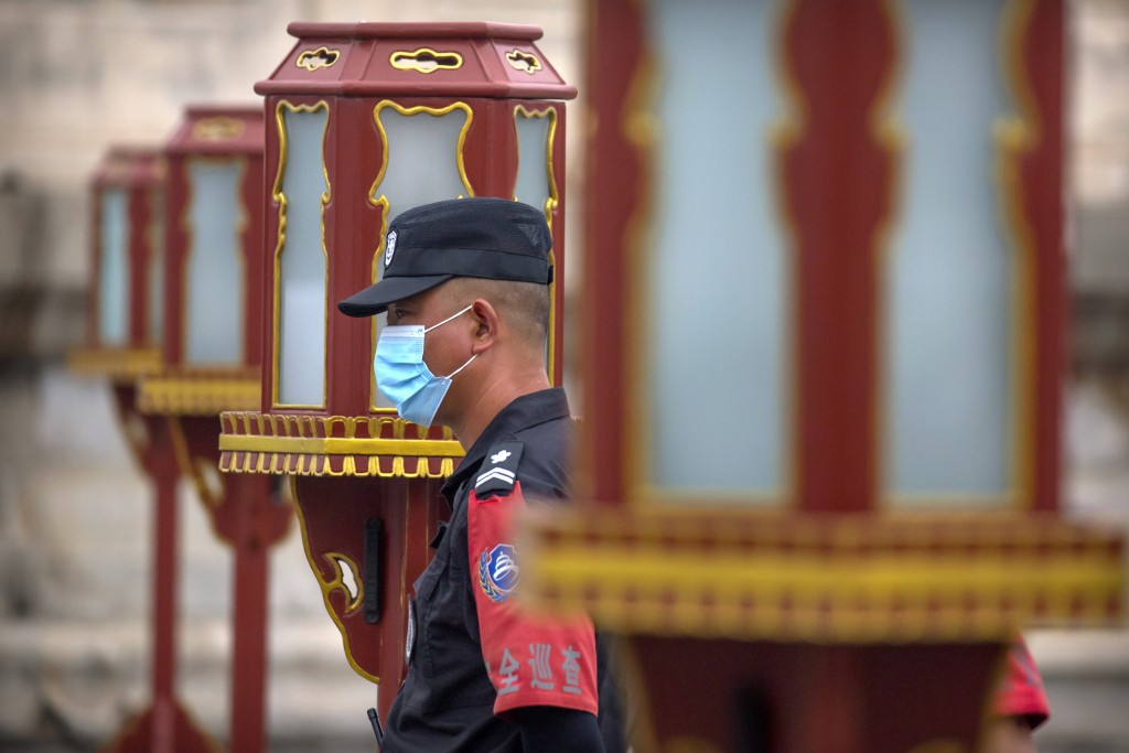 A security officer wearing a face mask to protect against the coronavirus stands guard at the Temple of Heaven in Beijing, Saturday, July 18, 2020. Au...