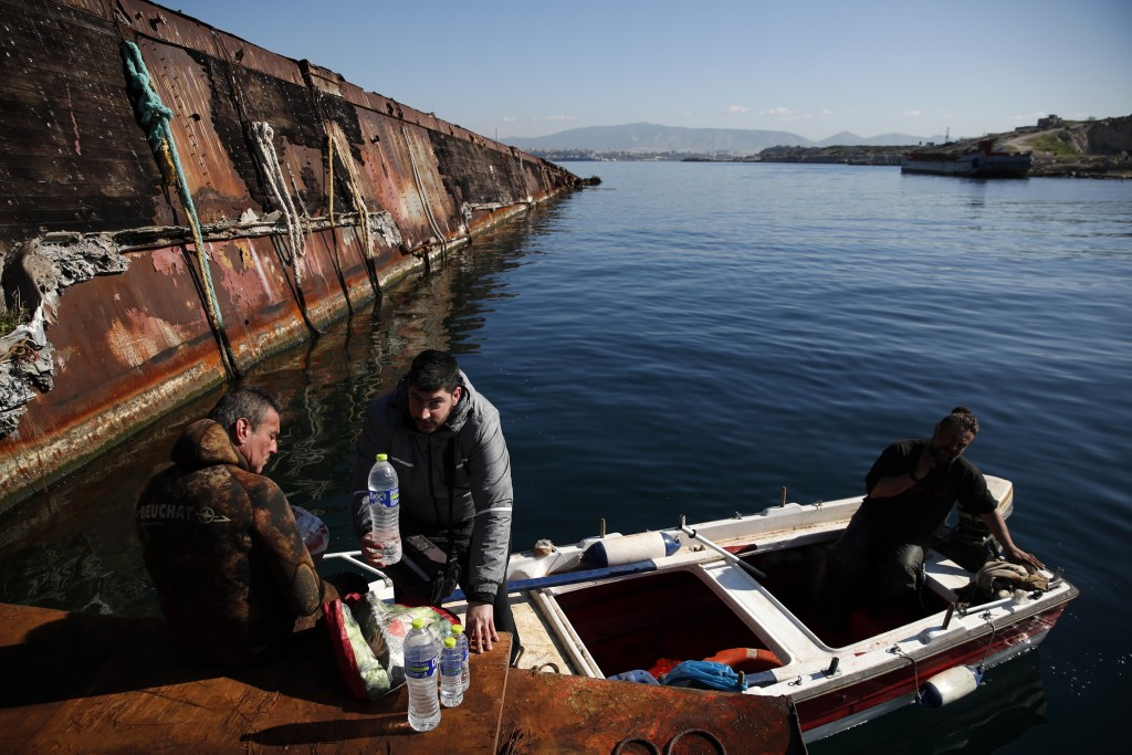 A diver takes a break as a delivery boy brings coffee and water to the crew during a shipwreck raising operation, on Salamina island, west of Athens, ...