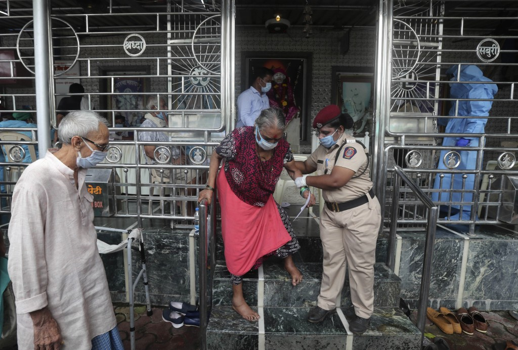 An elderly woman walks down a flight of stairs, helped by a policewoman, after she gave her swab sample, at a temple in Mumbai, India, Saturday, July ...