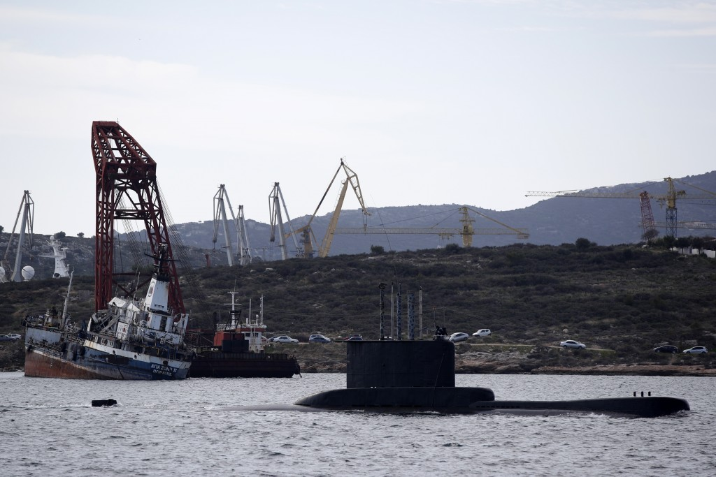 A submarine approaches its naval base as a half sunken ship is seen near a shipyard on Salamina island, west of Athens, on Tuesday, Feb. 12, 2020.  Gr...