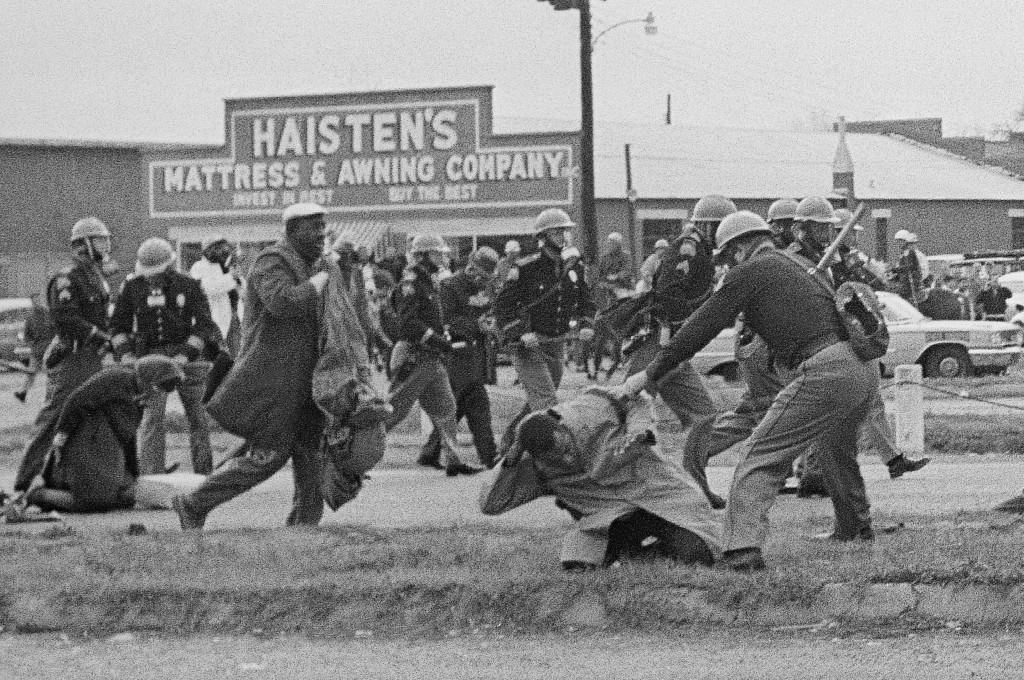 FILE - In this March 7, 1965, file photo, a state trooper swings a billy club at John Lewis, right foreground, chairman of the Student Nonviolent Coor...
