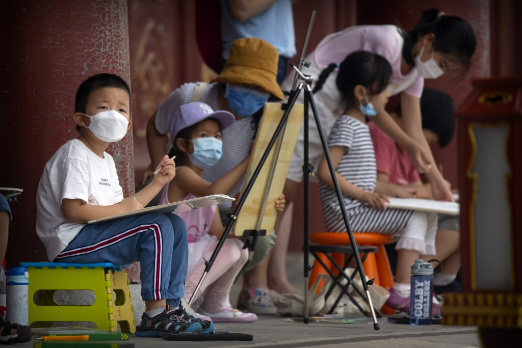 Children wearing face masks to protect against the coronavirus sketch the Temple of Heaven in Beijing, Saturday, July 18, 2020. Authorities in a city ...