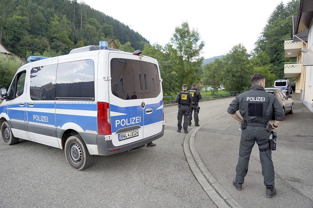 Police officers stand in front of a driveway in a forest area near Oppenau, Germany, Friday, July 17, 2020. A man who disarmed four officers at gunpoi...