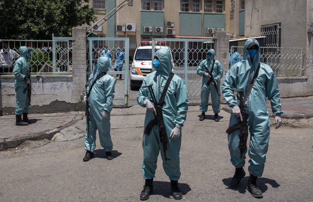 Palestinian Hamas police officers wear protective suits as they take part in a simulation of possible coronavirus infections in Gaza City, Saturday, J...