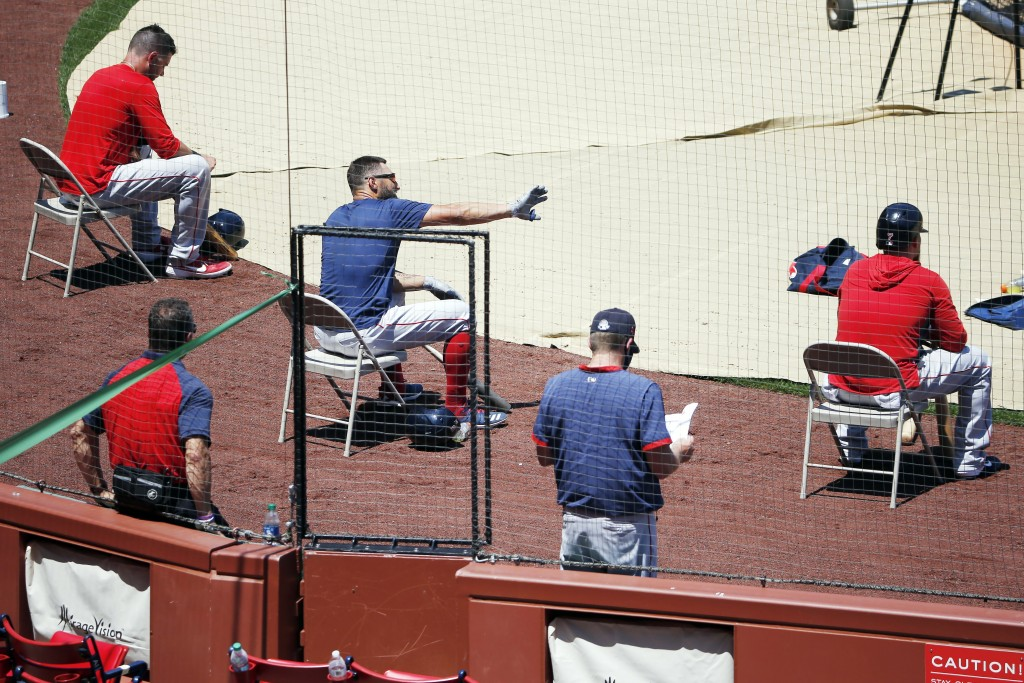 FILE - In this July 5, 2020, file photo, Boston Red Sox players sit apart for social distancing during baseball practice at Fenway Park in Boston. Pub...