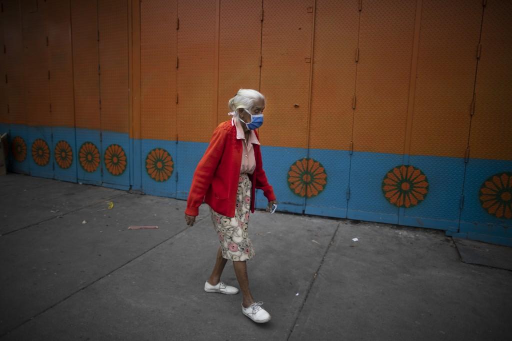 An elderly woman wearing a protective face mask walks on a street in Caracas, Venezuela, Friday, July 17, 2020, amid the new coronavirus pandemic. (AP...