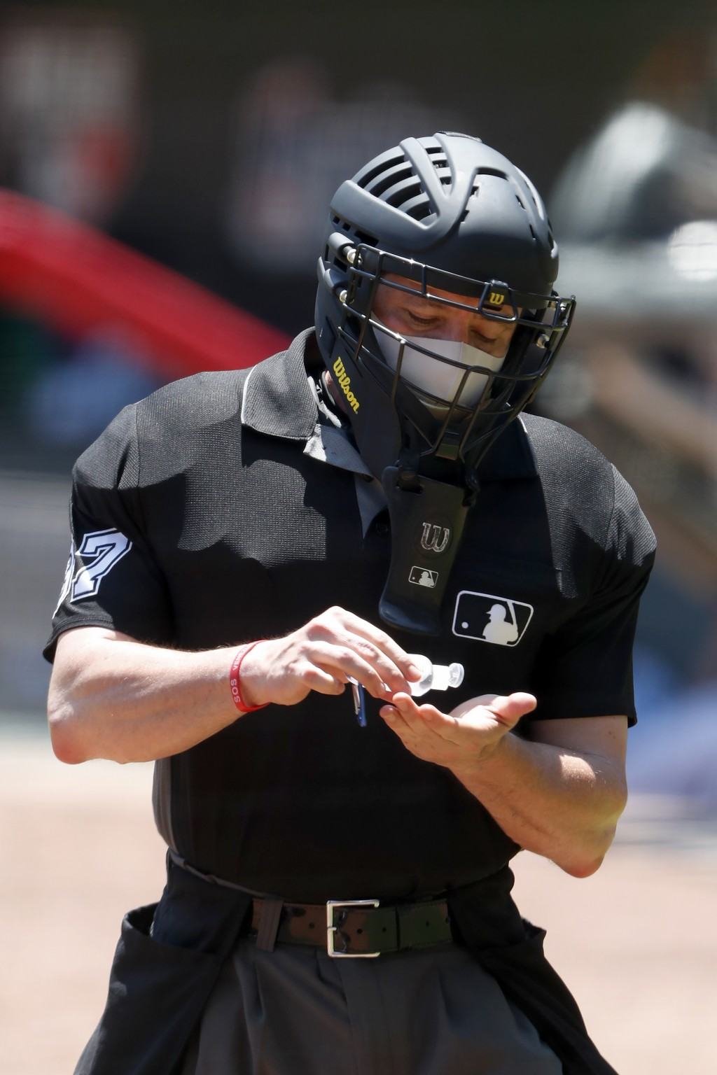 FILE - In this July 16, 2020, file photo, umpire Carlos Torres (37) sanitizes his hands between batters during an Atlanta Braves intrasquad baseball g...