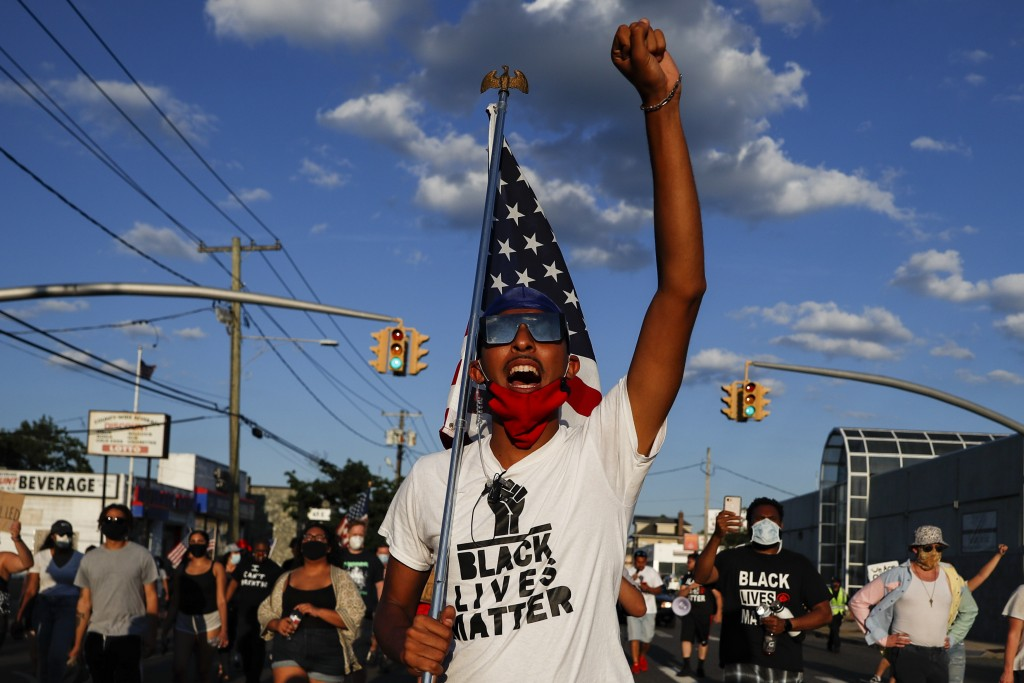 A protester carrying a U.S. flag leads a chant during a Black Lives Matter march through a residential neighborhood calling for racial justice, Monday...