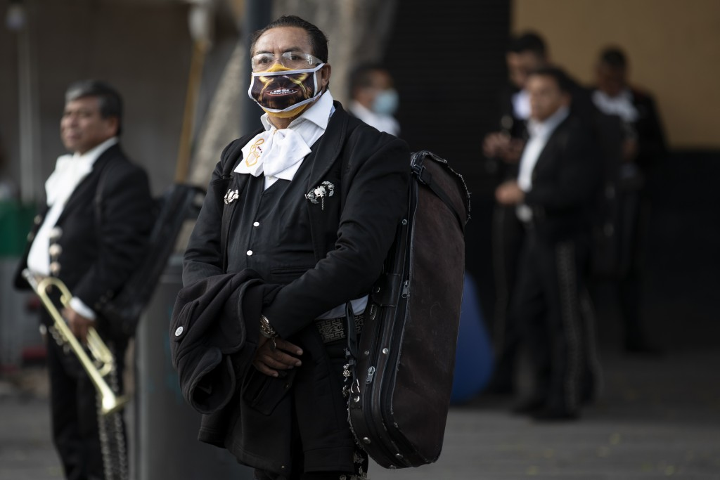Mariachis, some wearing protective face  masks, wait for clients in Plaza Garibaldi, where residents come to hire mariachis for events and parties, in...