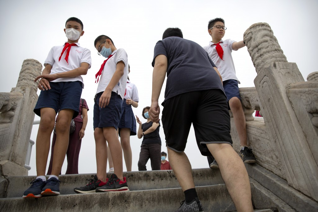 Students wearing face masks to protect against the coronavirus gather at the Temple of Heaven in Beijing, Saturday, July 18, 2020. Authorities in a ci...