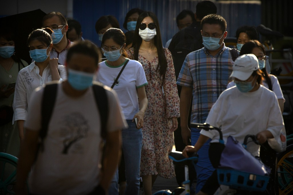 People wearing face masks to protect against the coronavirus wait to cross an intersection in the central business district of Beijing, Wednesday, Jul...