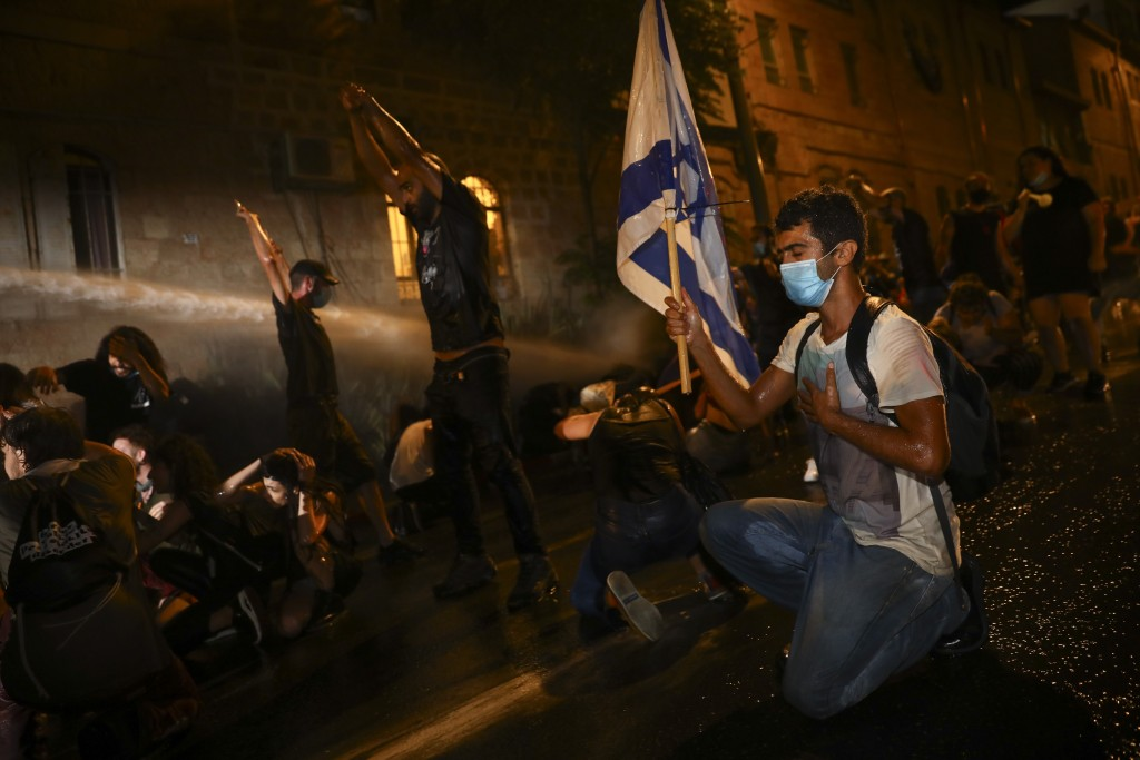 Israeli police uses water canon to disperse people during a protest against Israeli Prime Minister Benjamin Netanyahu In Jerusalem Saturday, July 18, ...