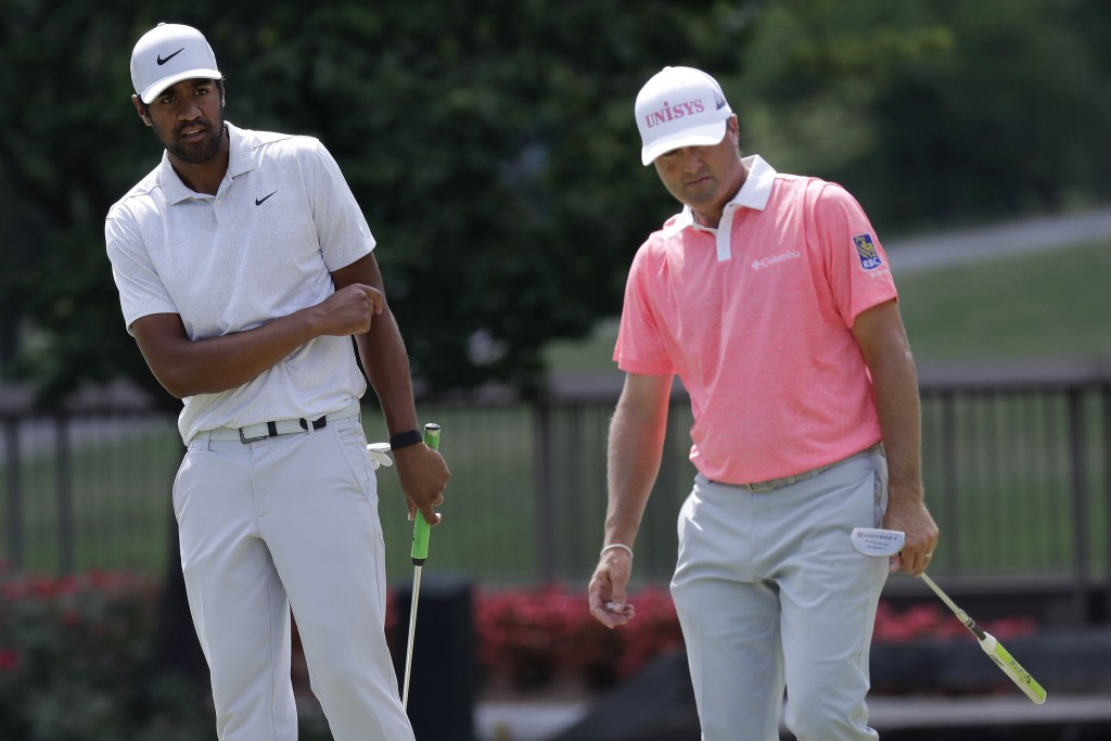 Tony Finau, left, reacts after missing a putt for birdie at the ninth hole next to Ryan Palmer during the third round of the Memorial golf tournament,...