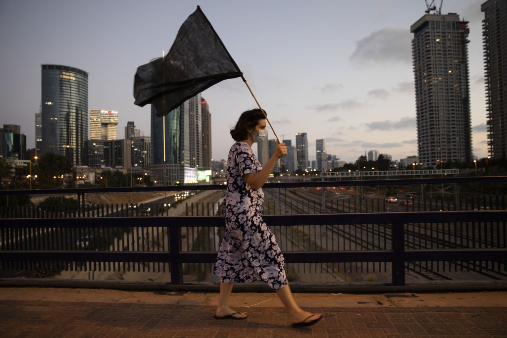 A woman wears a protective face mask, to protect against coronavirus, walks with a black flag during a protest against Israeli Prime Minister Benjamin...