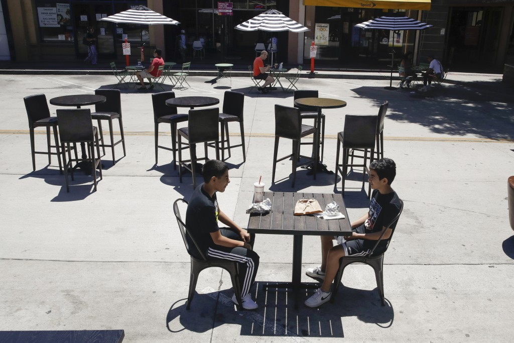 Young patrons eat a meal on a table set on a closed-off street Saturday, July 18, 2020, in Burbank, Calif. The city of Burbank has closed off some str...