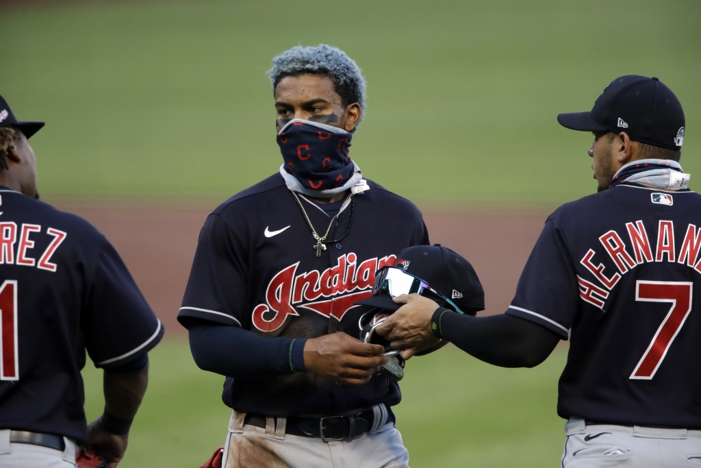 Cleveland Indians' Francisco Lindor, center, gets his glove and cap from Cesar Hernandez (7) at the end of the first inning of an exhibition baseball ...
