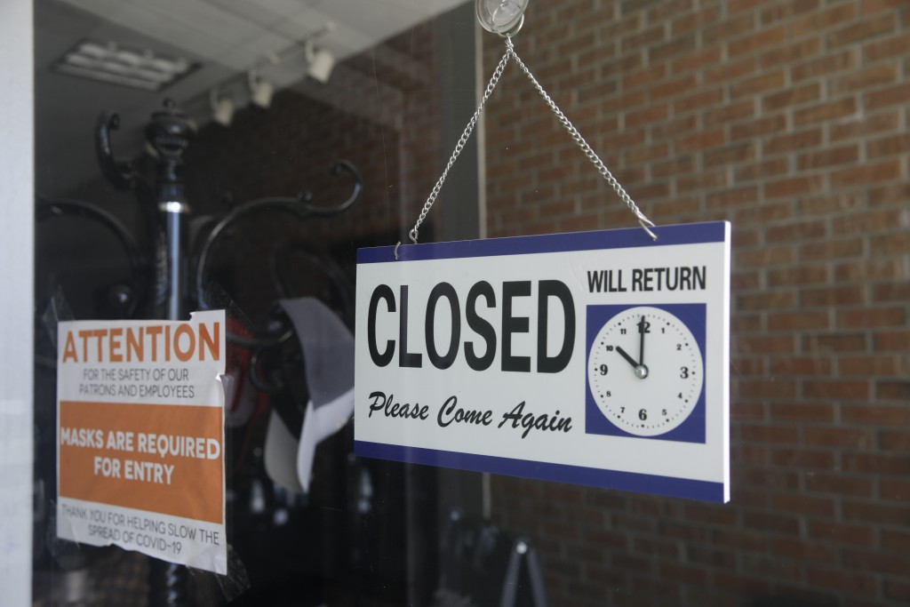 A closed sign is posted on the window of a barbershop Saturday, July 18, 2020, in Burbank, Calif. The city of Burbank has closed off some streets in t...