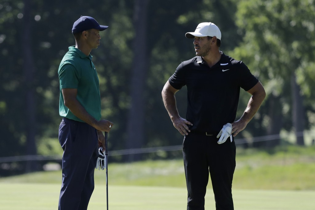 Tiger Woods, left, talks with Brooks Koepka on the 11th fairway during the third round of the Memorial golf tournament, Saturday, July 18, 2020, in Du...