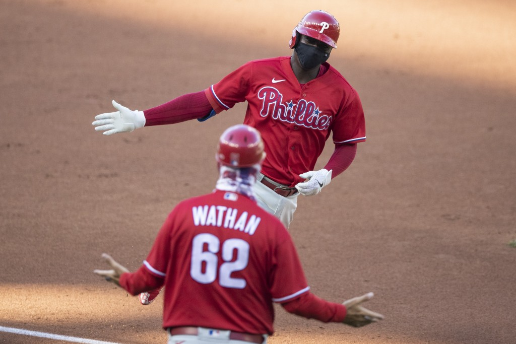 Philadelphia Phillies' Didi Gregorius celebrates with third base coach Dusty Wathan as he rounds the bases for his three-run homer during the first in...