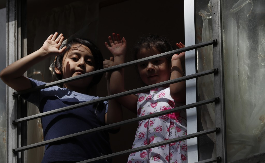 Residents wave from an apartment as Percibald Garcia reads children's books aloud outside the high-rise buildings in the Tlatelolco housing complex, i...