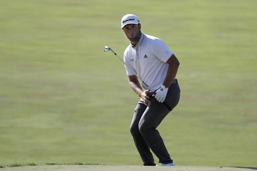 Jon Rahm, of Spain, watches his chip to the 18th green during the third round of the Memorial golf tournament, Saturday, July 18, 2020, in Dublin, Ohi...
