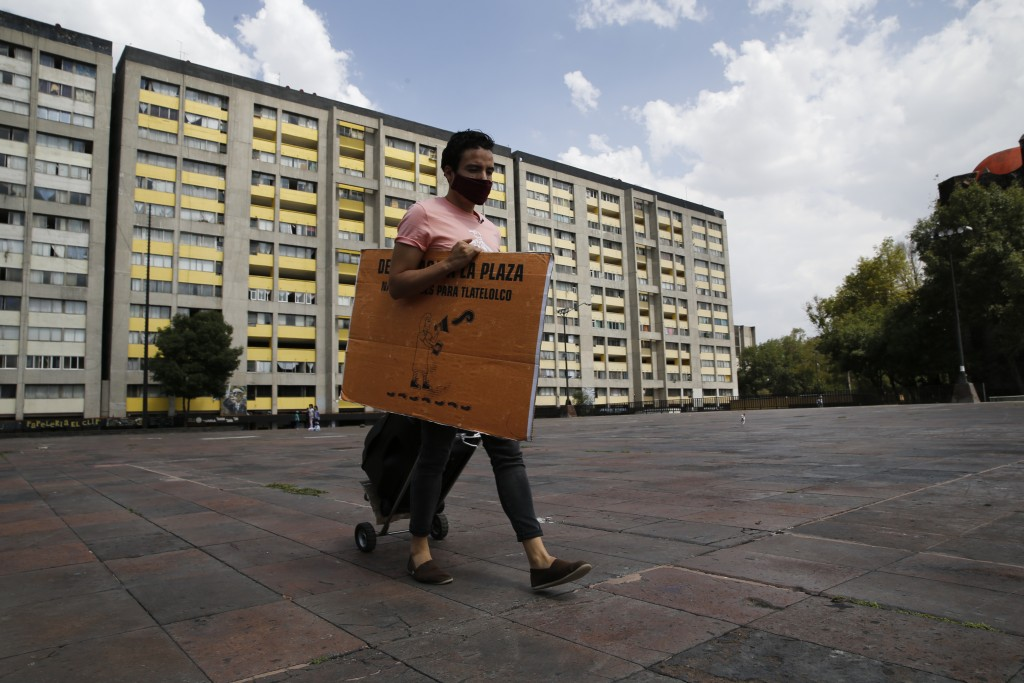 Percibald Garcia, who reads aloud children's books outside the high-rise buildings in the Tlatelolco housing complex, pulls a loudspeaker as he walks ...