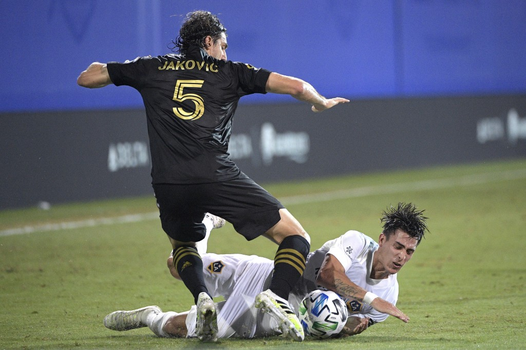 Los Angeles FC defender Dejan Jakovic (5) and LA Galaxy forward Cristian Pavon compete for the ball during the first half of an MLS soccer match Satur...